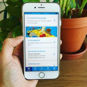 Hand som håller i en mobil med Nodras app igång