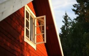 foto av husfasad i solsken med öppet fönster