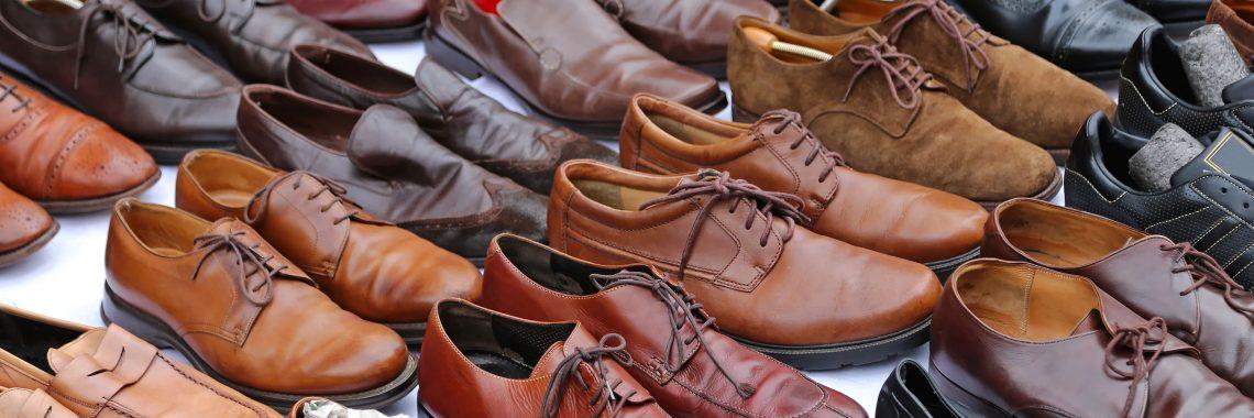 Fyra rader av tätt ställda herrskor i olika nyanser av läderbrunt.