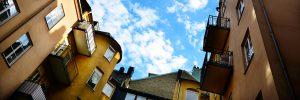 Flerfamiljhus fotade nerifrån upp mot en blå himmel med vita moln