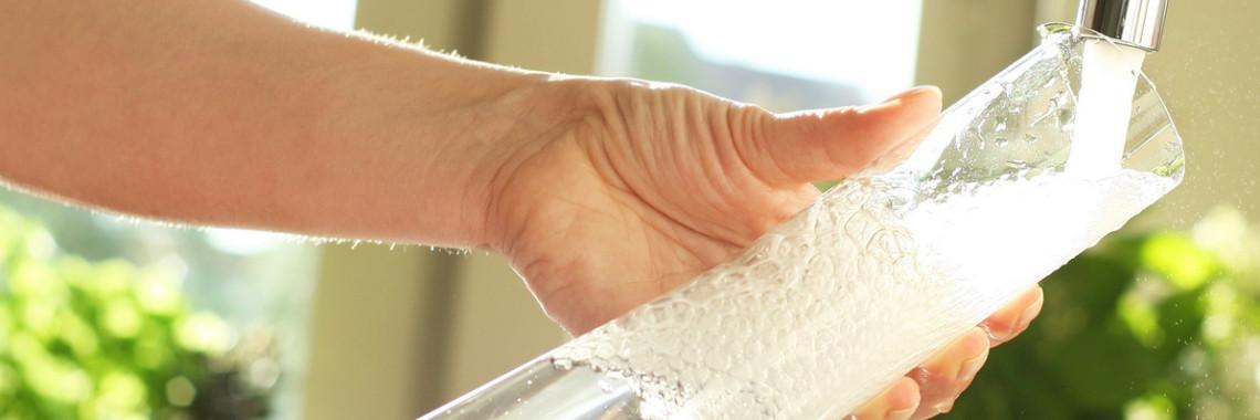 Foto av hand som fyller på en karaff med vatten under spolande kran