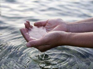 Foto som visar kupade händer i vatten.