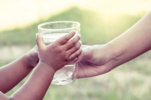Foto av vuxenhand som ger ett glas vatten till två barnhänder