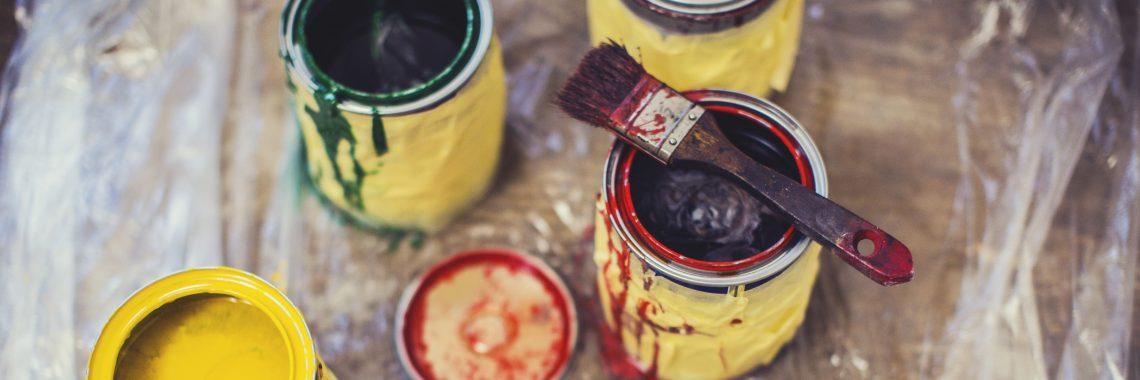 foto av öppna målarburkar där den ena har pensel på locket
