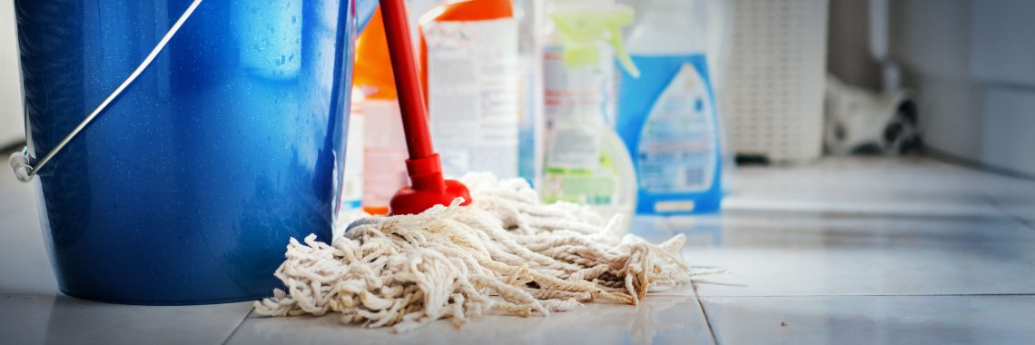 En blå hink, en mopp och rengöringsprodukter på ett golv.