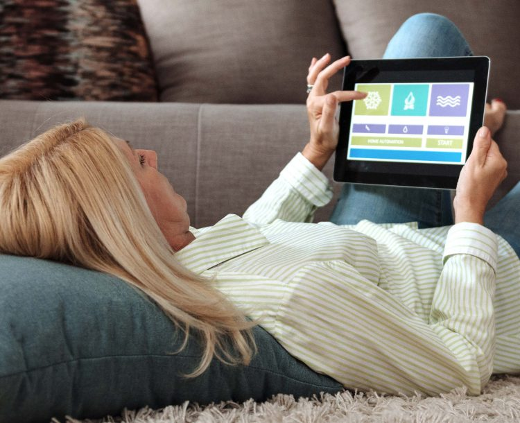 Kvinna som ligger på golvet med huvudet på en kudde och fötterna på soffkanten och använder en surfplatta för att styra smarta tjänster i hemmet.