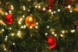 Julgran med lampor och röda och gula kulor