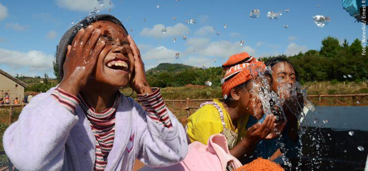 Glada barn som tvättar ansiktet i vatten