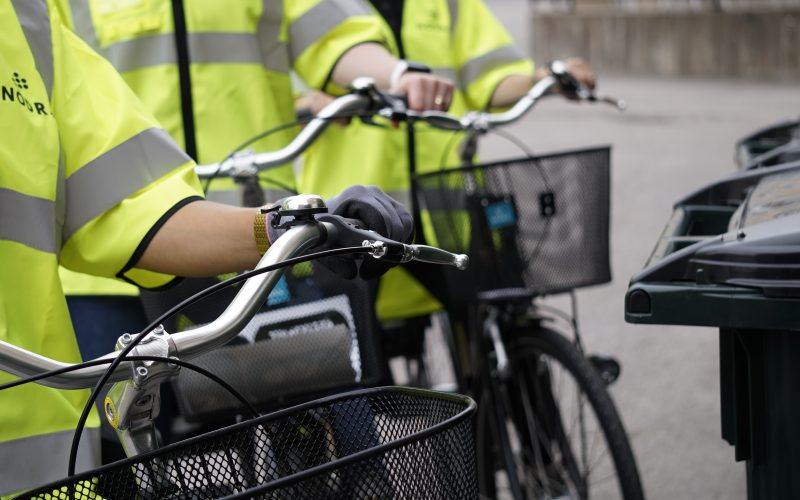 tre personer vid cyklar och soptunnor