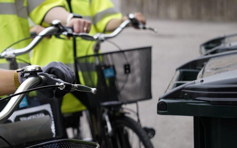 Närbild av händer på cykelstyren bredvid två soptunnor