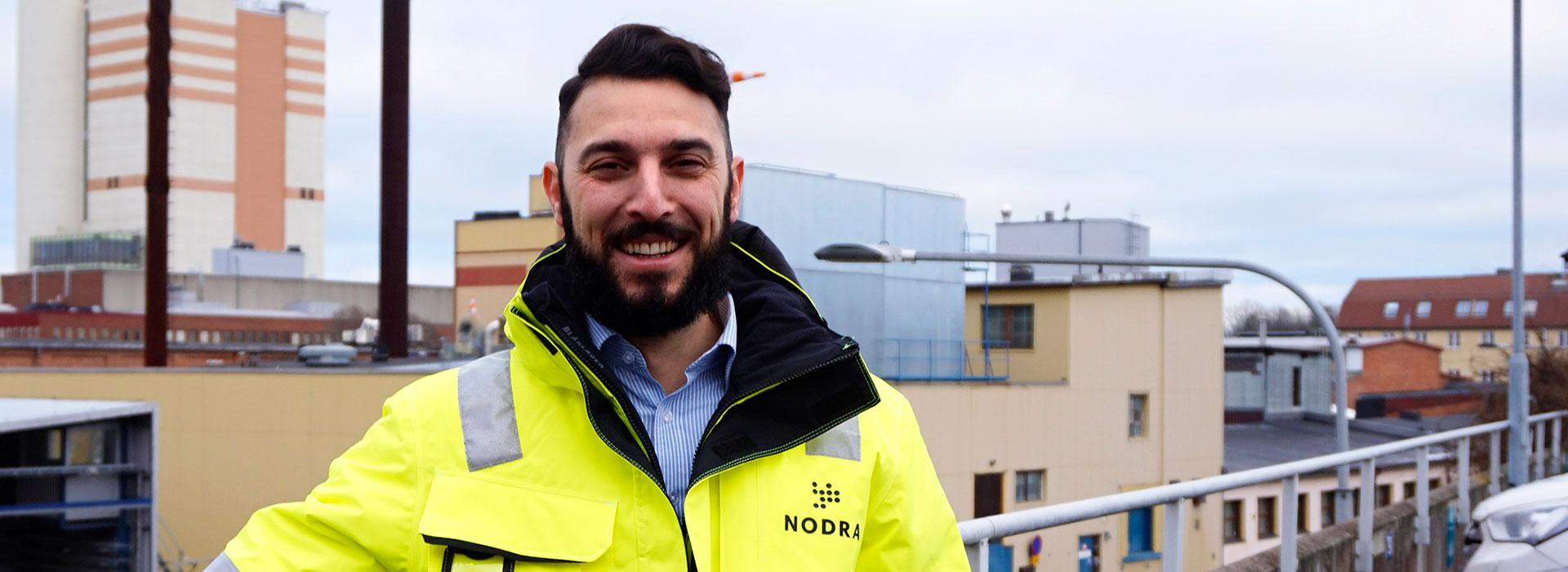 Porträtt på en man som har en varseljacka med Nodras logotyp. Bakgrunden är en vy över byggnader och hustak