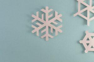 Snöflingor gjorda i papper på en ljusblå bakgrund