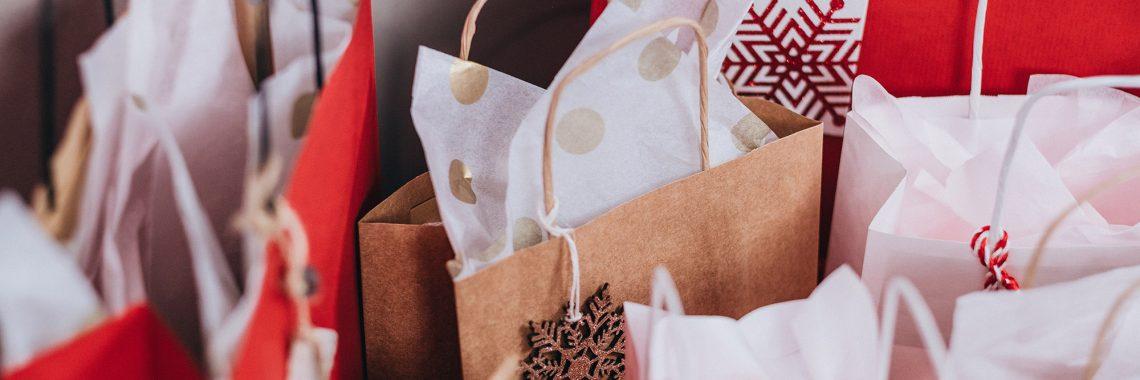Flera papperspåsar med presentpapper dekorerat med snöflingor som sticker upp ur dem.