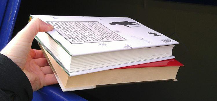 Hand som håller i böcker