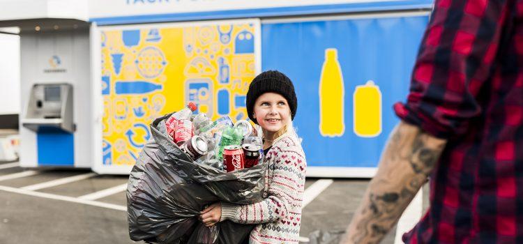 Flicka med en säck med pantflaskor framför pantmaskin