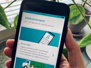 Hand som håller i en mobiltelefon där Nodras app visas