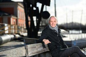 VD Henrik Peterson sitter på en bänk vid strömmen i Norrköping