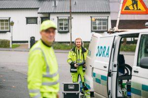 Två kollegor i varselkläder står vid en skåpbil med Nodra-logga på