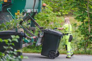 kvinna i arbetskläder tömmer soptunna i sopbil