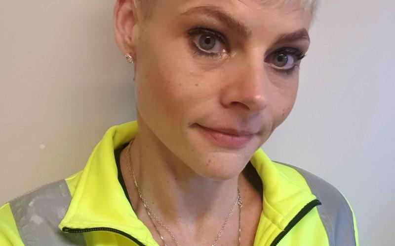 Porträttbild på Helena i en gul jacka med Nodras logotyp på