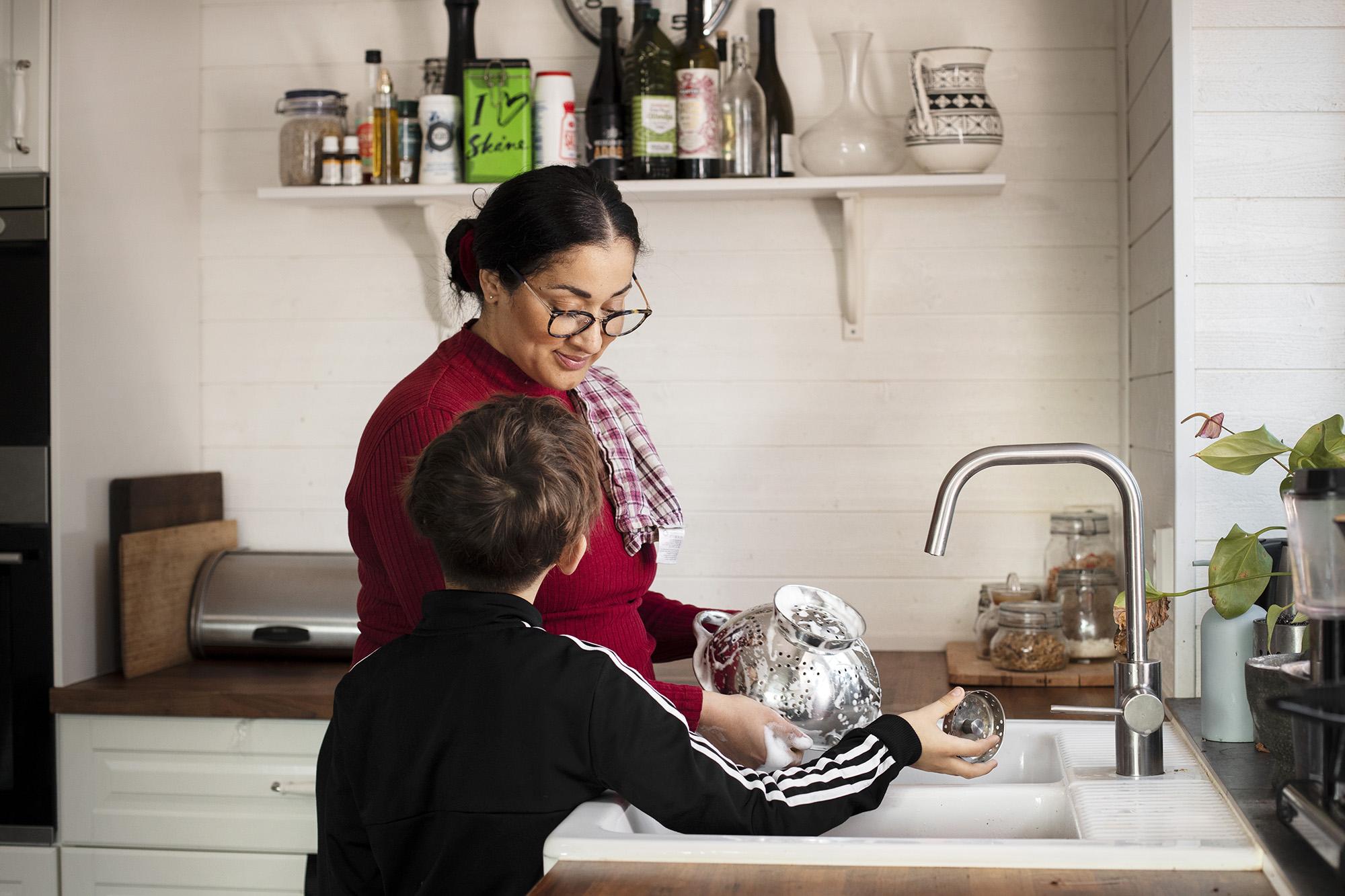 En kvinna och en pojke som står vid en diskho och diskar tillsammans