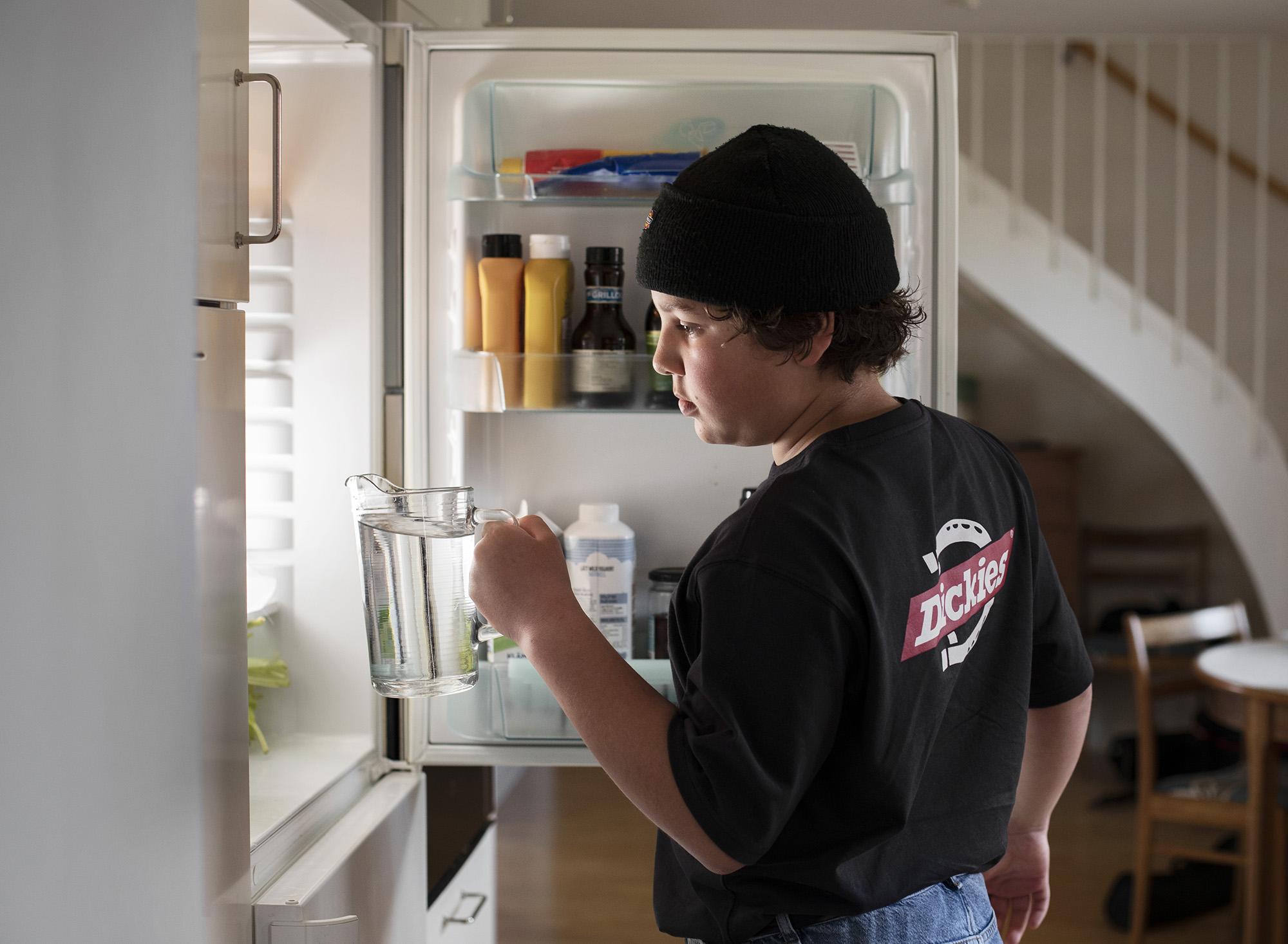 Pojke som har öppnat en kylskåpsdörr och ställer in en karaff med vatten