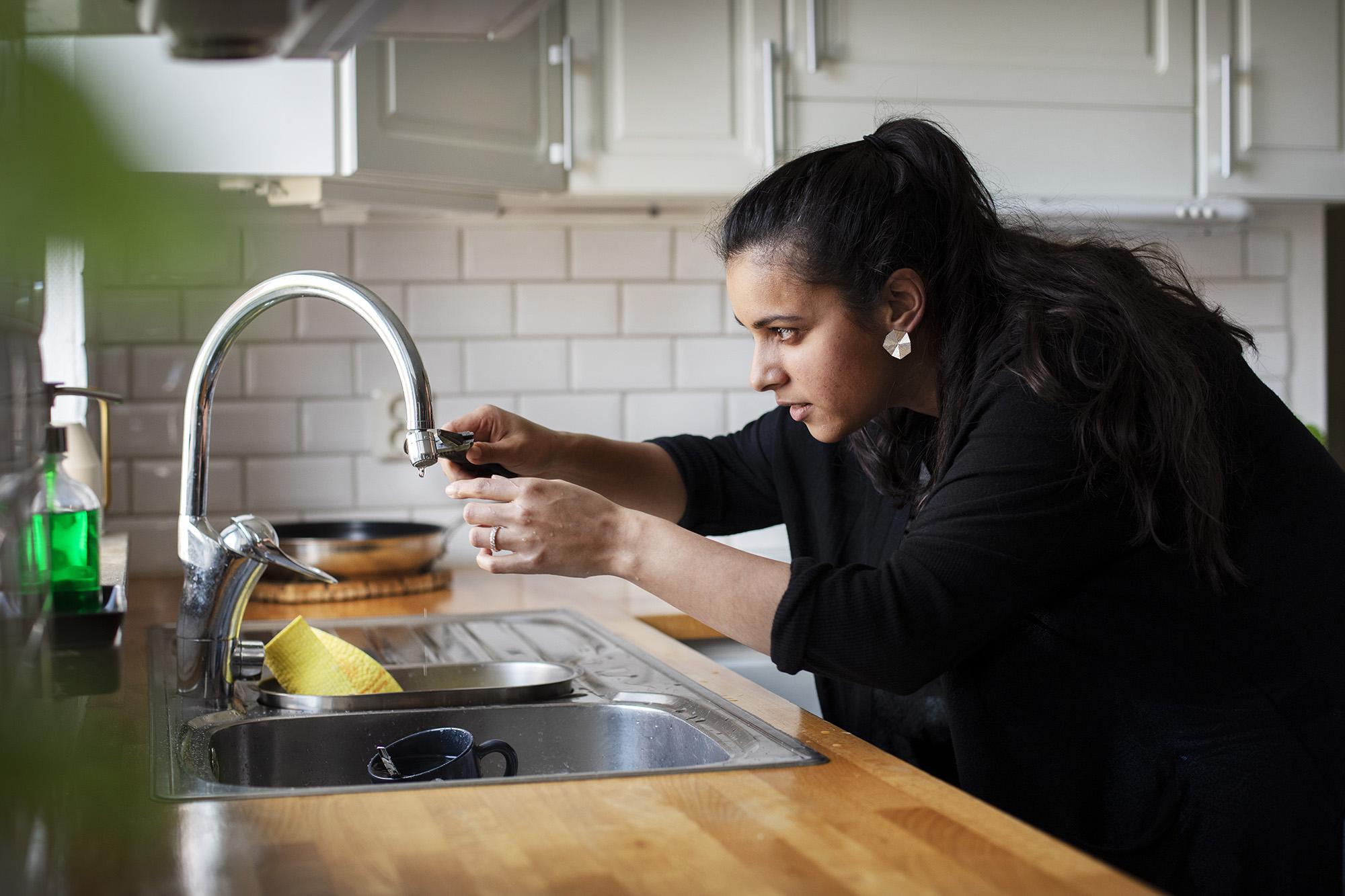 Kvinna som drar åt packningen till en kran i köket