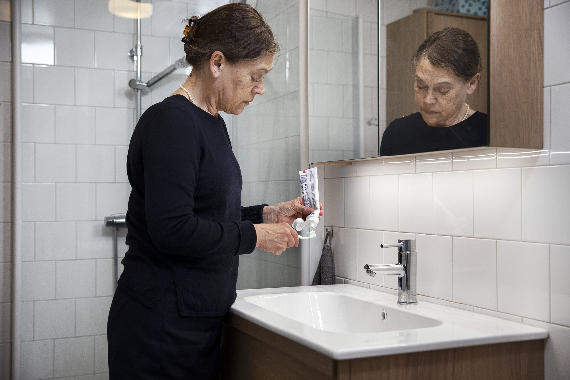 Kvinna som står i ett badrum och håller i en tub med tandkräm och en tandborste