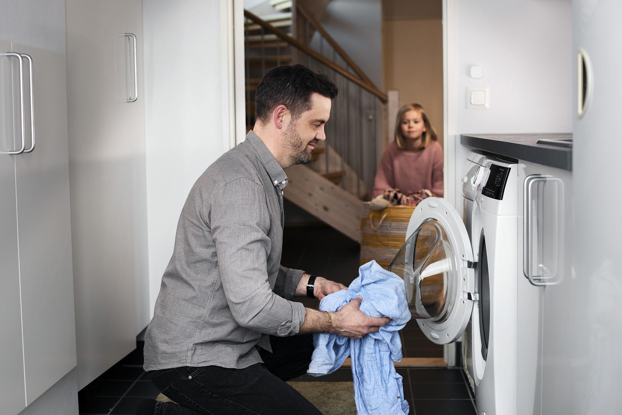 En man är på väg att lägga in ett blått klädesplagg i en tvättmaskin. I bakgrunden står en flicka med en tvättkorg.